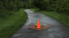 Orange pylon warns of damage on path. Stock Footage