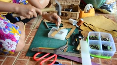 Thai woman punching hole and cutting for made handmade bag leather and key ring Stock Footage
