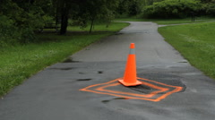 Orange pylon warns of damage on path. - stock footage