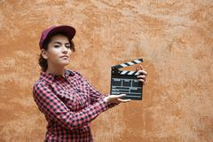 Young woman with movie clapper behind orange wall - stock photo
