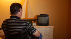 DISABLED-PARAPLEGIC: Man in wheelchair turns on old tv set Stock Footage