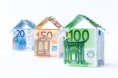 Three houses made of bank notes Stock Photos