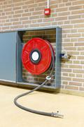 Red fire hose on reel at wall Stock Photos