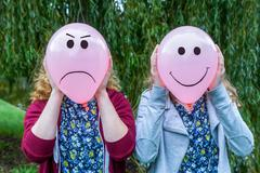Two girls holding balloons with facial expressions - stock photo
