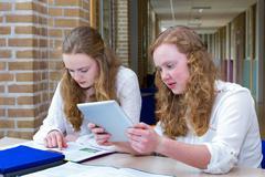 Two dutch teenage girls studying in long school corridor Stock Photos