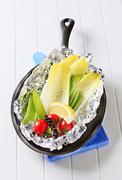 Still life of fresh vegetables on tinfoil in skillet Stock Photos