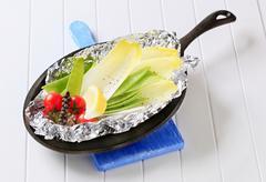 Still life of fresh vegetables on tinfoil in skillet - stock photo