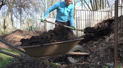 Farm worker with pitchfork dig compost and carry full barrow. 4K Stock Footage