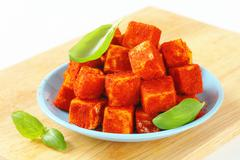 Diced cheese rolled in paprika powder Stock Photos