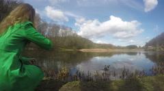 Blond girl with green coat feeding duck birds near lake. 4K Stock Footage