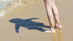 3762 Ocean Waves Going Over Childs Shadow and Feet with Arms Wide Open Stock Footage