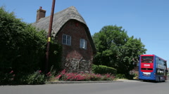 Old thatched cottage in anEnglish village bus pulling away Stock Footage