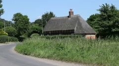 Old fashioned thatched cottage on rural road in england Stock Footage