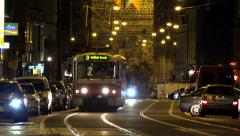 Night city - urban street with cars and trams - people walking Stock Footage