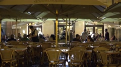 Night restaurant in the city - outdoor seating - people sitting Stock Footage