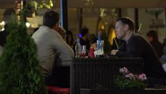Two men sitting in a restaurant and talking - urban street with walking people Stock Footage