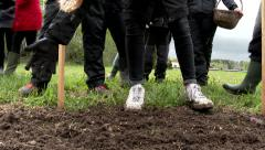 A group of schoolboys and girls in a farm learning how to plant seeds. Stock Footage