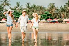 Group of happy young people walking along the beach on beautiful summer sunset Stock Photos