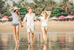 Group of happy young people walking along the beach on beautiful summer sunset - stock photo