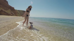 Girl throws a stone into the water and the dog Jack Russell swims in the sea Stock Footage