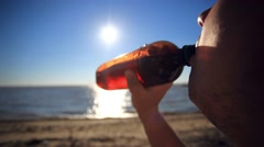 Young man sit back and relax at the beach in sunset time. Drinks beer on The sun Stock Footage