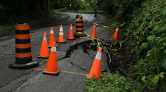Orange pylons warning of road damage due to flood erosion. Stock Footage