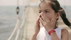 Child sneezes on pier in ocean Stock Footage