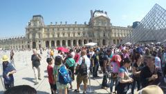 People outside the Louvre museum on a summer day Stock Footage