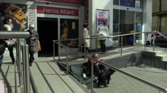 Senior man homeless in city begging, drinking alcohol and barking dog Stock Footage