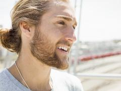A young man with beard, red hair and ponytail. - stock photo