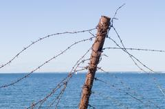 Old barbed wire fence and rusty post against sea and sky - stock photo