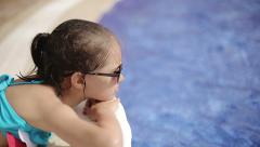 Child lies on a sun lounger by the pool at the hotel Stock Footage