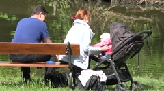 Family relax near pond - mather and father with baby sit on bench - closeup Stock Footage