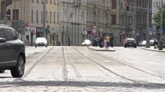 Urban street with pasing cars and tram in the city - building in the background Stock Footage