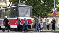 People get off tram and walk - tram leaves a station - urban street in the city Stock Footage