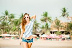 Stock Photo of Beautifil young woman walking along the beach at sunset enjoing summer vacation