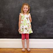 Beautiful little girl standing against blackboard at home Stock Photos