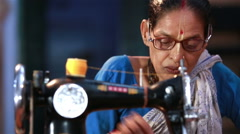 Elderly Indian woman sew clothes using mechanical sewing machines in the Ashram. Stock Footage