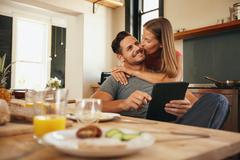 Woman giving good morning kiss to her boyfriend in kitchen Stock Photos