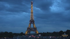 Illuminated Eiffel tower Paris night, intermittent lights, car traffic at dusk Stock Footage