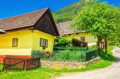 Wooden yellow hut and street in Vlkolinec Slovakia - stock photo