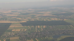 Green forest, small city village seen from airplane window, aircraft flight view - stock footage
