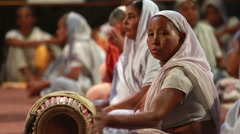 Indian woman in a sari plays a traditional drum during a religious rite Krishna. Stock Footage