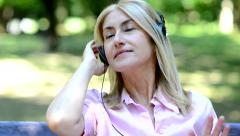 Woman listening music outdoors Stock Footage