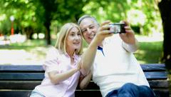 Couple taking a selfie in a park Stock Footage