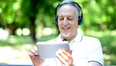 Man listening music in a park Stock Footage