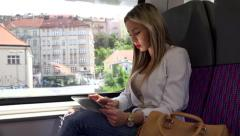 Young attractive blonde woman traveling by train and works on tablet Stock Footage