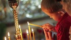 A boy lights a candle in church Stock Footage