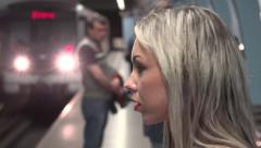 Young attractive blonde woman waits for subway and looks around - arriving metro Stock Footage