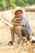 lonely orphan child sitting on the railroad - stock photo